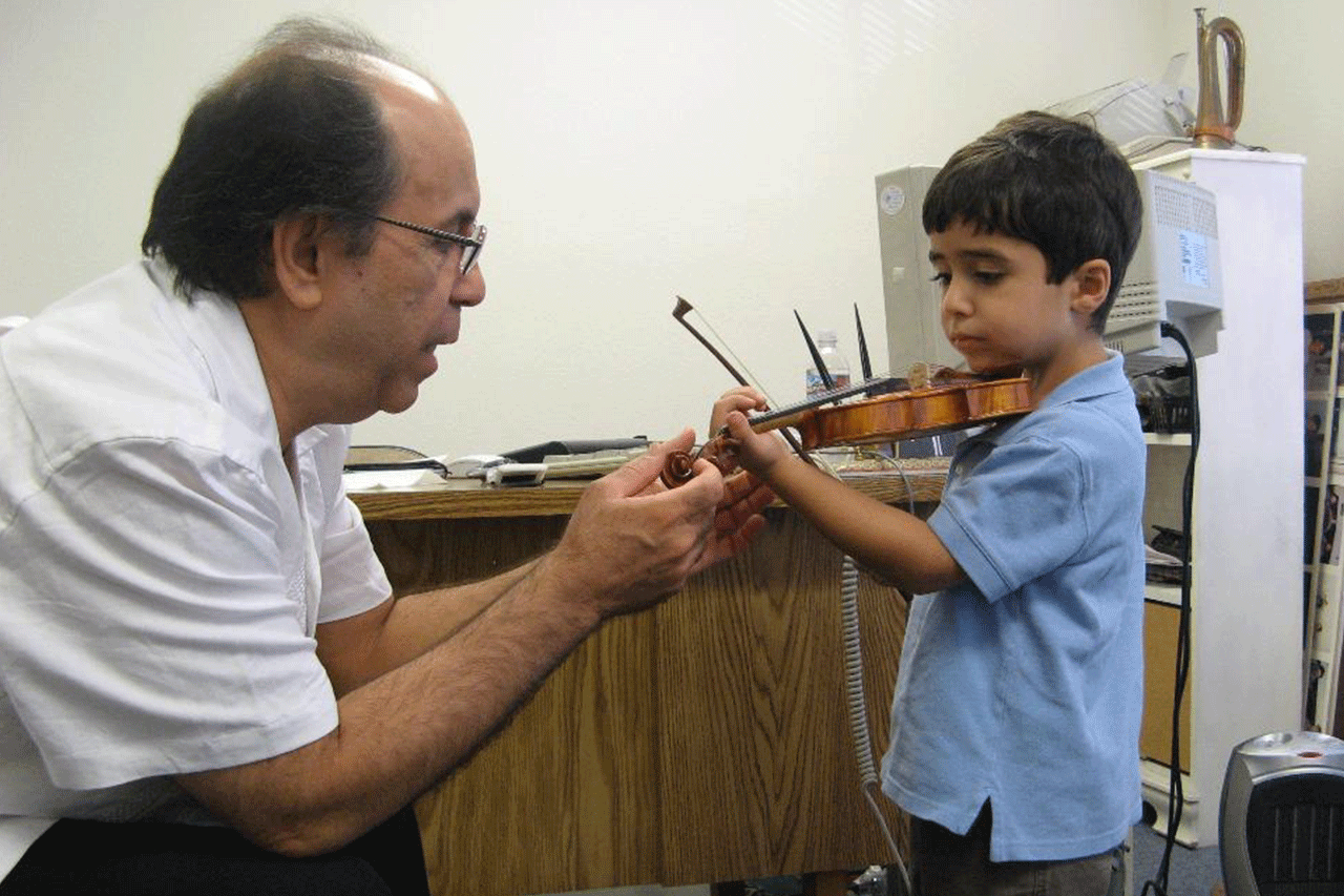 Loghman teaching violin at international music school